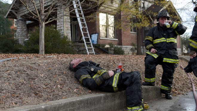 Firefighters Chris Schafer and Greg Baltz of Nashville Fire Engine 3 rest after fighting a fire at 1200 Ordway Place in Nashville on Thursday, Dec. 15, 2016.