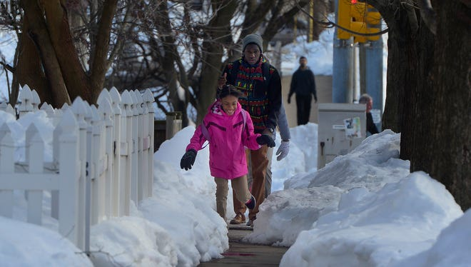 Sonjai Smith, 9, leads her brother Halman, 17, and sister Montika, 11, home along N. Beaver St. from school at Logos Academy, Thursday January 28, 2016. John A. Pavoncello photo