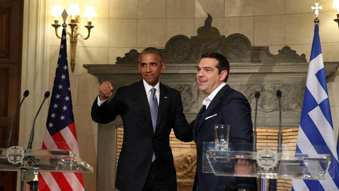 President Obama and Greek Prime Minister Alexis Tsipras smile after a news conference at Maximos Mansion in Athens Tuesday. Obama praised Greece for its financial commitment to NATO — and for being one of five NATO allies that dedicated at least 2% of its gross domestic product to defense spending.