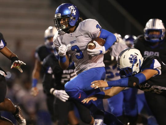 Trinity Christian Academy's Marcus Crowley scrambles past Godby's Trey Laing during their Region 1-5A Semifinal game at Cox Stadium on Friday, Nov. 17, 2017.