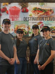 Kaleb Warnock and Paula Flores-Warnock, right, are opening Tropical Smoothie Cafe at 1513 N. Zaragoza. Employees Mitzie, center left, and Kayla Ramirez pose with them inside the restaurant.