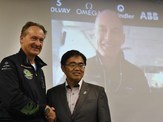 Solar Impulse 2 pilot Andre Borschberg, left, shakes