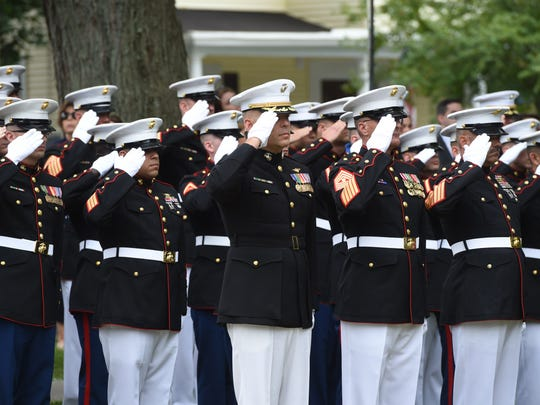 Members of the U.S. Marine Corps salute as the casket