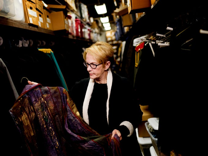 Marianne Custer holds a hand-painted garment in a storage