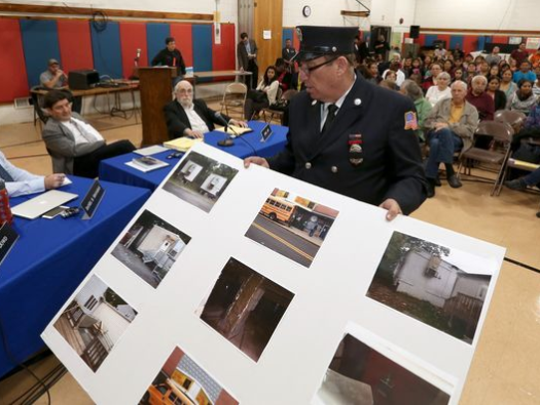 Justin Schwartz, head of the Rockland Illegal Housing Task Force, displays photos of schools with violations.