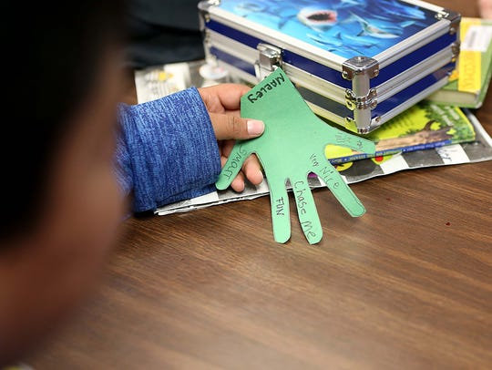 A second-grader at Irion County Elementary holds a classmate's hand cutout after writing one thing nice about them on a finger.