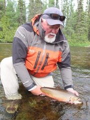 Chris Hunt prepares to release a brook trout caught on the Albany River system in northwestern Ontario.