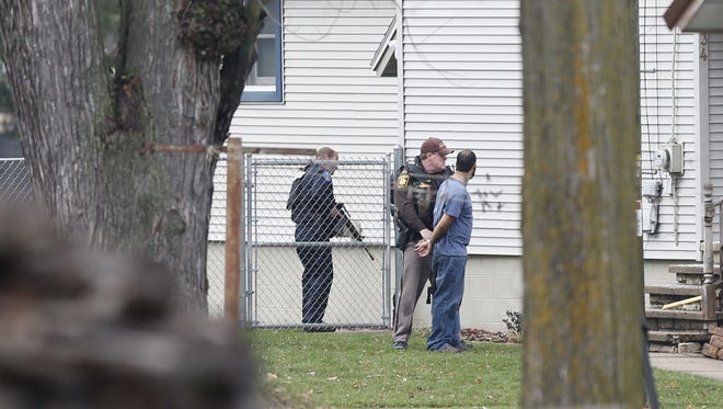 Police officers handcuff a man in Waupun after establishing a perimeter around the home on Rounsville Street.