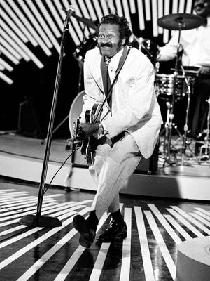 American guitarist and singer Chuck Berry performs his 'duck walk' on stage as he plays his guitar on April 4, 1980.  The location is not known.