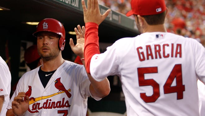 St. Louis Cardinals' Matt Holliday, left, is congratulated by teammate Jaime Garcia after scoring a run on a single by Allen Craig during the fourth inning of a baseball game against the Arizona Diamondbacks on Wednesday, May 21, 2014, in St. Louis.