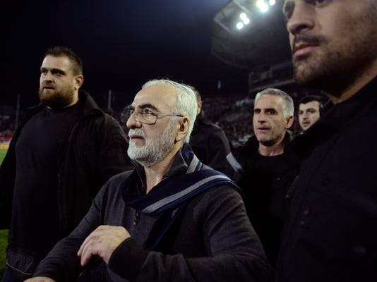 In this Sunday, March 11, 2018 photo, PAOK owner, businessman Ivan Savvidis, center, walks on the pitch escorted by his bodyguards during a Greek League soccer match between PAOK and AEK Athens in the northern Greek city of Thessaloniki, Sunday, March 11, 2018. A disputed goal at the end of the Greek league match led to a pitch invasion by Savvidis, who appeared to be carrying a gun.  (AP Photo)