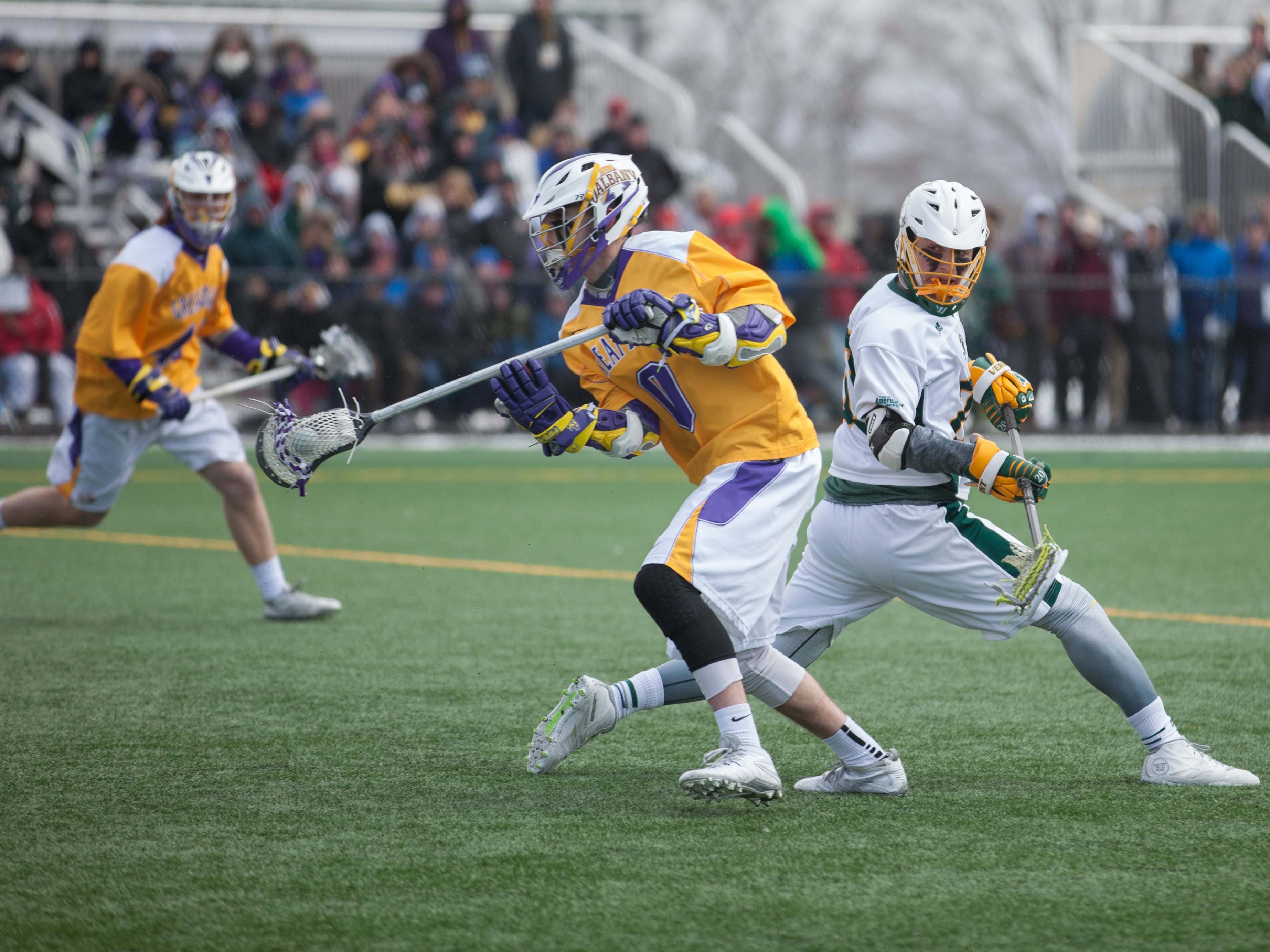Albany's John Maloney, left, runs past Vermont's Bryan Capone during a men's lacrosse game at Virtue Field on Saturday.