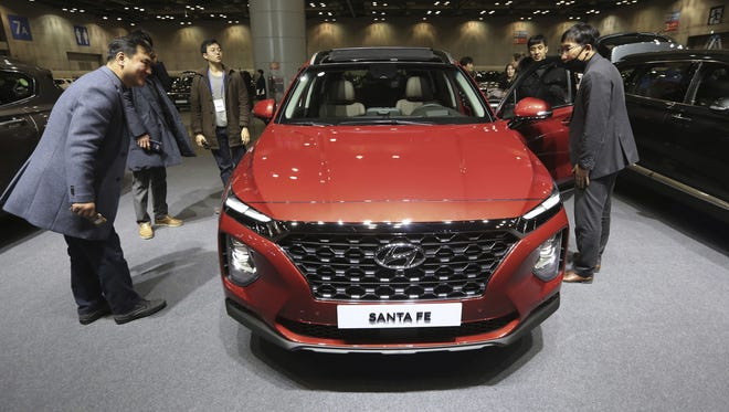 Members of the media view Hyundai Motor's all-new Santa Fe sport utility vehicle during a press unveiling at KINTEX exhibition center in Goyang, South Korea, Wednesday, Feb. 21, 2018.