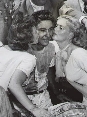 Bill Vukovich winner of the 1954 Indianapolis 500 is kissed by his wife (left) and movie star Marie Wilso.