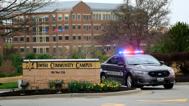 A police car is seen at the entrance to the Jewish Community Center of Greater Kansas City in Overland Park, Kan., where two of a gunman's three victims were shot April 13.