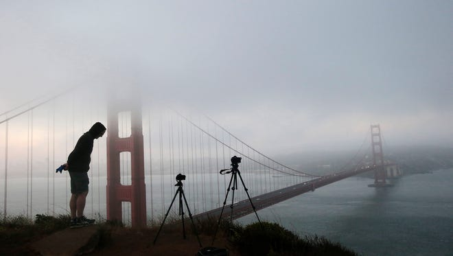 Russell Brown of Los Altos, Calif., photographs the fog-covered Golden Gate Bridge from  a hill in the Marin Headlands in San Francisco.