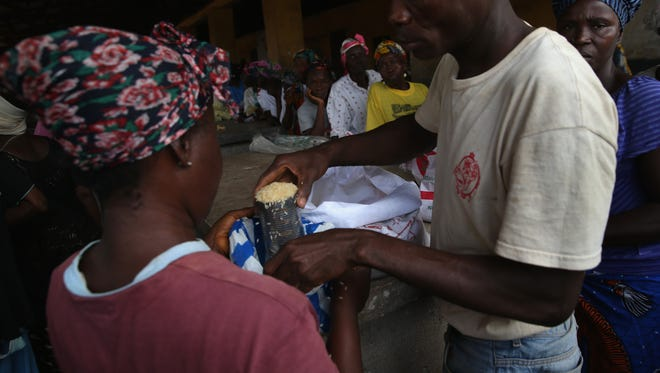 Residents line up to receive a ration of 9 cups of rice each at a distribution center on Aug. 23, 2014, in Dolo Town, Liberia.