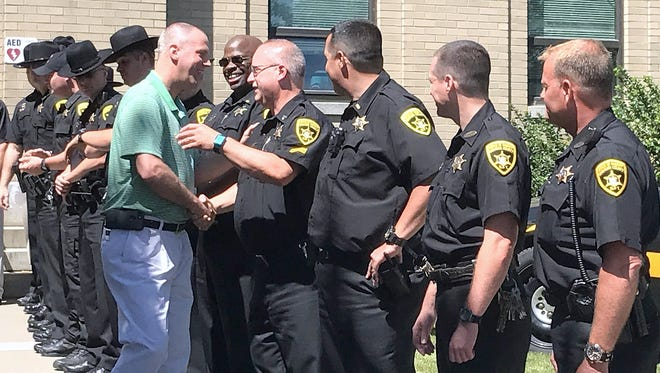"""Retiring Chemung County Sheriff's Office Capt. Douglas Houper greets colleagues during his official """"walkout"""" ceremony Friday."""
