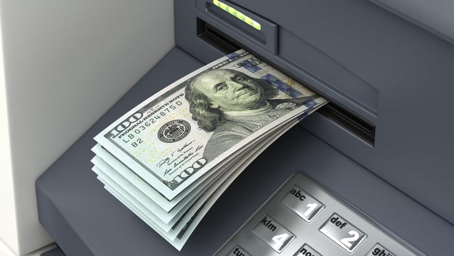 An ATM is spitting out a bunch of hundred-dollar bills.