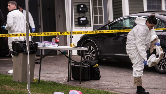 Vermont State Police investigators work at 10/12 Southview Drive in South Burlington on Friday, May 4, 2018, after authorities discover a woman shot to death inside on of the two apartments there. Police are searching for Leroy A. Headley who is a suspect in the woman's death.