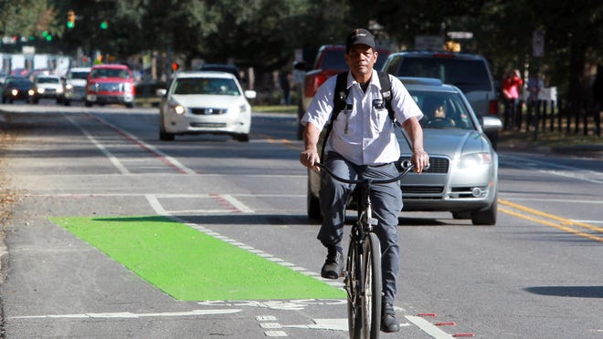 Wilfred Rue uses one of the recently created bike lanes on St. Mary Boulevard as he leaves his job at the Petroleum Club in the Oil Center Friday. Leslie Westbrook February 20, 2014