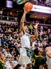 Lourawls Nairn, left, of MSU lays the ball in as he