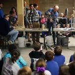 Missouri State University Engineering faculty Matthew Pierson sets up a bucket of sand to test the strength of a wooden bridge made by a student at the Academy of Exploration on Thursday, Feb. 11, 2016. Students from Hickory Hills Elementary and the Academy of Exploration showcased model bridges and presentations created by over 100 fifth-graders and held a bridge breaking competition.