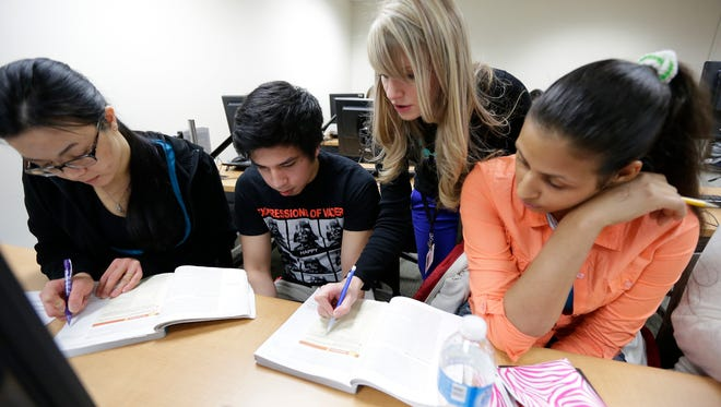 Reading instructor Kristin Sericati, center, works with students, from right, Lilibel Diaz, Charlington Borabon and Neng Xiong.