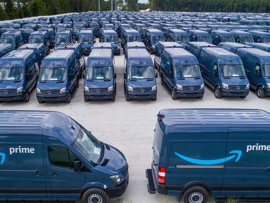 Dozens of blue vans marked with Amazon Prime logo.