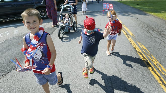 From left, Sodus Point residents Carson Hogan, 6; Knox Frisbie, 5; and Ailey Hogan, 4, march during the Red, White and Blue Kiddie Parade on Friday in Sodus Point, Wayne County. Children in costume marched from the Sodus Point Fire Hall to the pavilion of the Sodus Bay Lighthouse Museum.