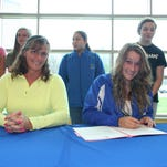 Harper Creek swimming standout Kara Popps, right, signs a National Letter of Intent to go to Saginaw Valley State University. She is joined by her mother and coach Corrin Popps, as well as members of the Harper Creek swim team.