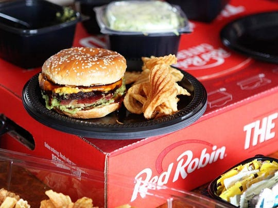 A burger and potato chips on a plate sitting on top of a Red Robin box