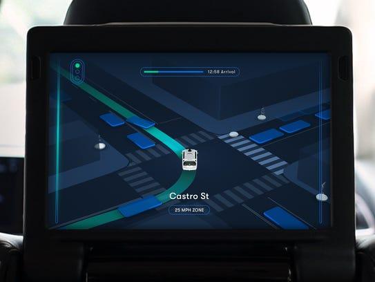 Riders in the back seat of a Waymo driverless minivan