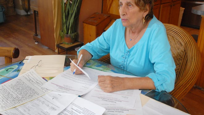 Mary Matkin, 83, at home in Rockledge with some of the paper work connected to the scam that she was a victim of.