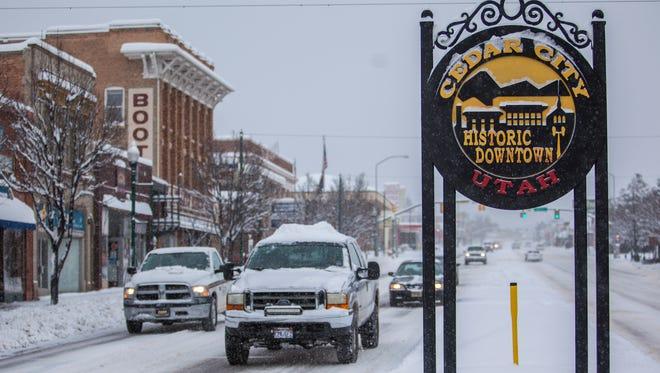 Cars drive down a snowy Main Street in Cedar City, Monday, Feb. 1, 2016.