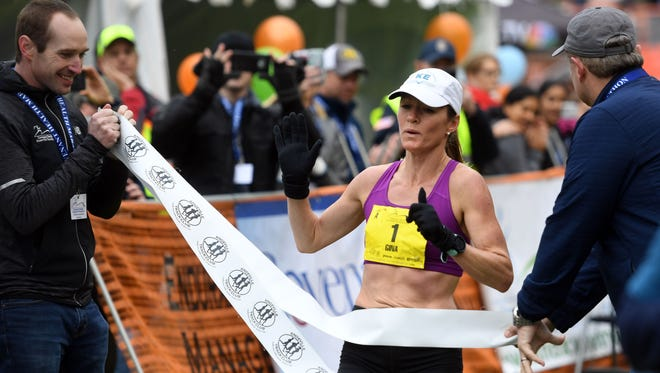 Gina Rouse crosses the finish line of the Covenant Health Knoxville Marathon with a time of 2:56:30 on Sunday.