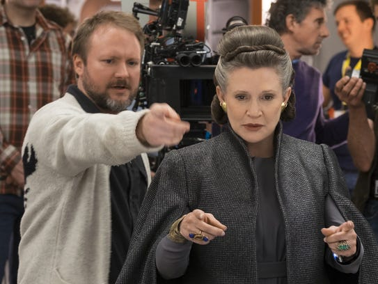 Director Rian Johnson goes over a scene with Carrie