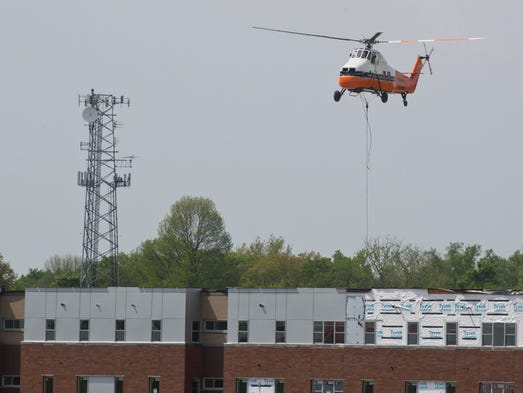 A helicopter lifts one of twelve HVAC units Monday, May 19, 2014, in West Lafayette. The copter lifted the units from the ground to the roof of a new residential building being built across the street from Mackey Arena.