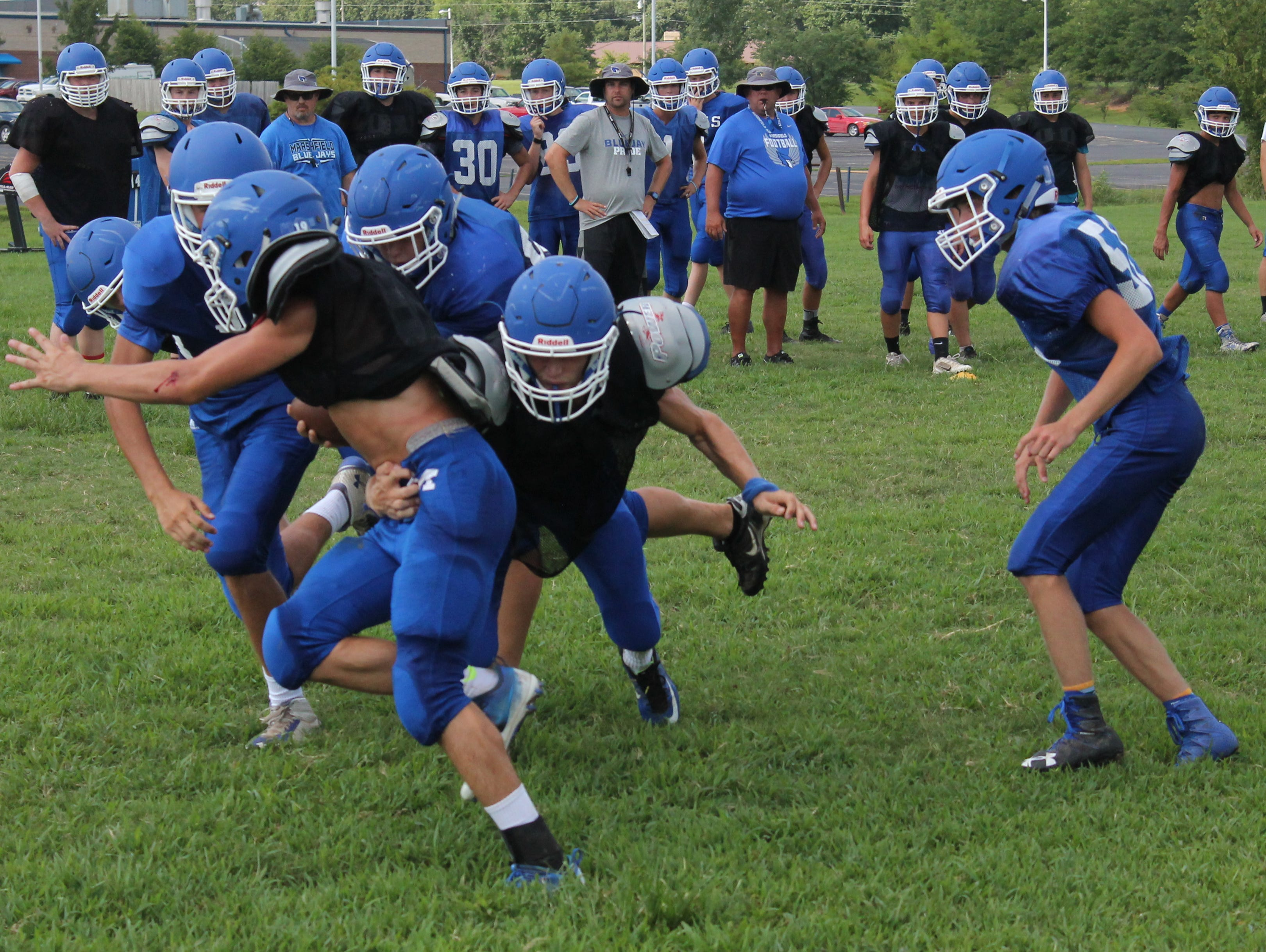 Marshfield's Chris Crotinger tackles a teammate during a practice drill Aug. 8, 2016 at Marshfield High School.