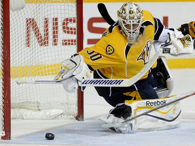Nashville Predators goalie Carter Hutton scrambles to cover the puck against the Buffalo Sabres during the second period at Bridgestone Arena on March 27, 2014.