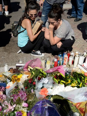 Crystal Fernandez, left, and Carmen Arias share a moment at a memorial that sprung up on a median on Las Vegas Blvd. near the Mandalay Bay Hotel and Casino in Las Vegas on Oct. 4, 2017.