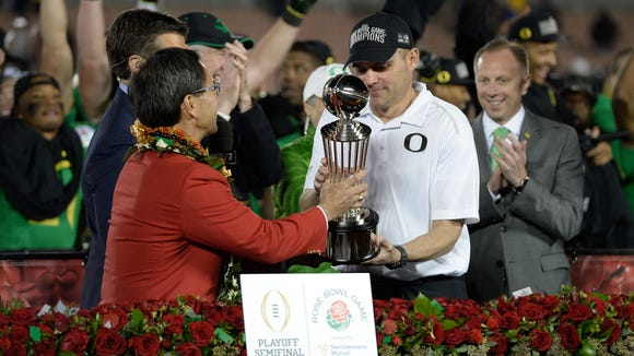 Jan 1, 2015; Pasadena, CA, USA; Tournament of Roses president Rich Chinen and ESPN announcer Rece Davis present the Leishman Trophy to Oregon Ducks head coach Mark Helfrich after the Oregon Ducks defeated the Florida State Seminoles in the 2015 Rose Bowl college football game at Rose Bowl. Mandatory Credit: Kelvin Kuo-USA TODAY Sports