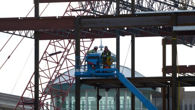 Workers frame and install steel decking as part of the KI Convention Center expansion project on Nov. 17 in downtown Green Bay.