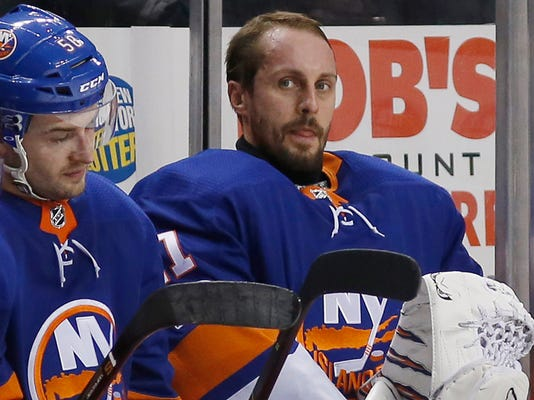 New York Islanders goalie Jaroslav Halak of Slovakia, right, sits on the bench beside Islanders defenseman Adam Pelech (50) after Halak was pulled from the game during the second period of an NHL hockey game against the Dallas Stars in which he allowed four goals, Wednesday, Dec. 13, 2017, in New York. The Stars defeated the Islanders 5-2. (AP Photo/Kathy Willens)
