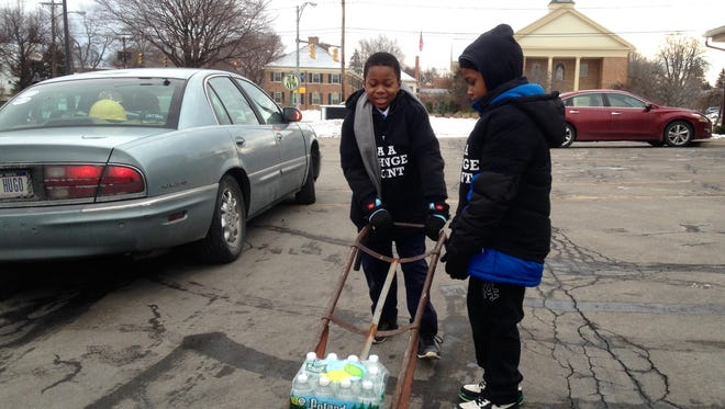 Joshua West, 8, of Greece, left, helps load water with Jeremiah Johnson, 8, of Rochester  on Saturday.
