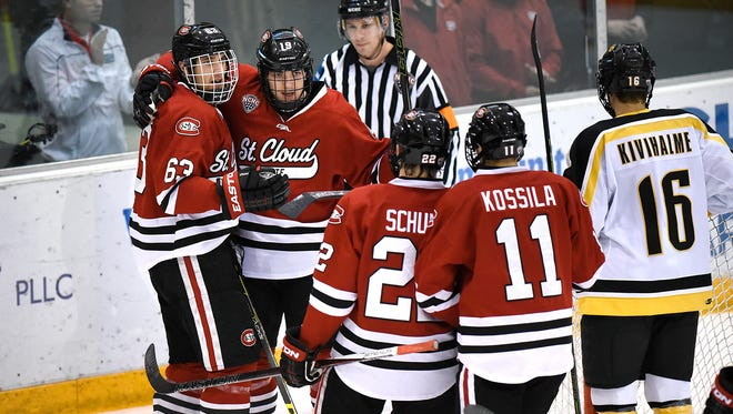 Kalle Kossila (11)  skates to congratulate Patrick Russell (63) on scoring goal Jan. 8 at the Herb Brooks National Hockey Center. Russell and Kossila have been a dynamic duo for the Huskies, combining for 19 goals, 30 assists and a plus-28.
