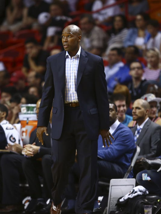 Orlando Magic coach Jacque Vaughn watches game action against the Miami Heat during the first half of  a NBA basketball game in Miami, Oct. 7, 2014. (AP Photo/J Pat Carter)