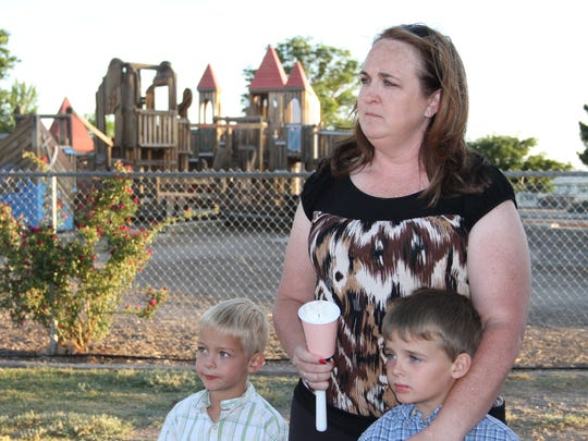 In this file photo from May, Melanie Gilmore and her two sons Ethan and Baker paid their respects to Ashlynne Mike at Kids Kingdom Playground during a vigil.