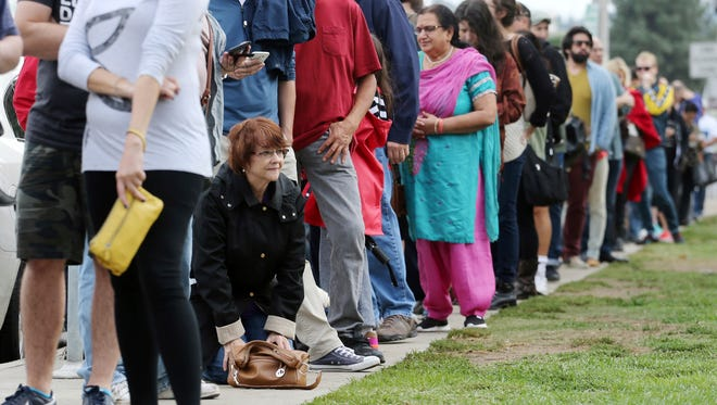 """FILE - In this Oct. 30, 2016 file photo, a woman kneels to take a """"back break"""" while waiting in line at a weekend early voting polling place at the North Hollywood branch library in Los Angeles. The FBI's disclosure that it was reviewing emails related to Hillary Clinton's email investigation will make no difference to tens of millions of voters who have already cast ballots."""