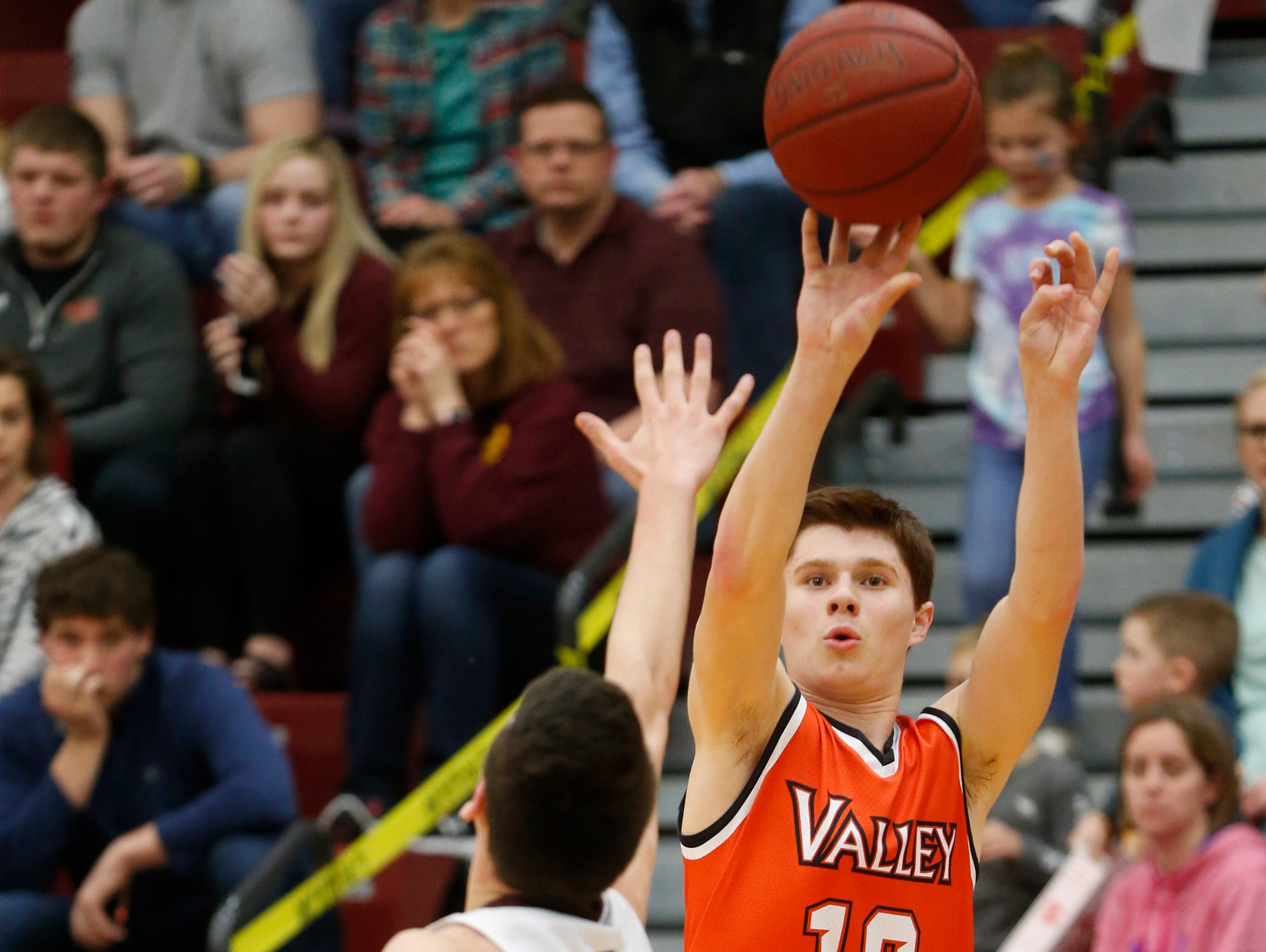 Valley senior Reese Skinner (12) shoots for three over Ankeny junior Ben Lyon (14) Friday, Feb. 10, 2017, at Ankeny High School in Ankeny.
